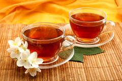 Te i koppar för ett exponeringsglas med jasmin blommar på matt bambu Royaltyfria Foton