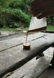 Te i koppen som häller vid handen arkivfoto