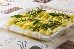 Te koken braadstukaardappels (ingrediënten: zout, rozemarijn, salie, olie, boter, kruiden) Stock Afbeelding