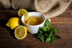 Te med citronen och mintkaramellen på trätabellen Arkivbilder