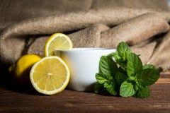 Te med citronen och mintkaramellen på trätabellen Arkivbild