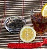 Te med delen av en citron nära ett exponeringsglas med te Fotografering för Bildbyråer