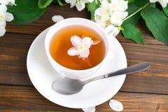Te med jasmin i en vit kopp på en trätabell Royaltyfria Bilder