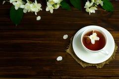 Te med jasmin i en vit rånar på en trätabell Royaltyfri Fotografi