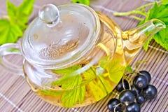 Te med svarta vinbär i den glass tekannan på bambu Arkivfoto