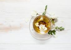 Te med trädgårds- rosor i en genomskinlig kopp arkivbild