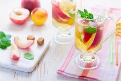 Te och ingredienser för sommardrinkpersika sött arkivfoton