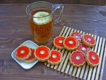 Te och kakor med röd gelé royaltyfri bild