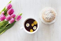 Te och muffin med gr?na stekheta koppar med tulpan royaltyfri foto