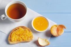 Te och rostat bröd med mandarindriftstopp royaltyfri bild