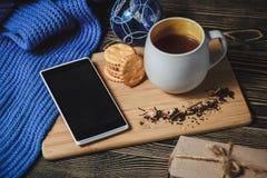 Te och smartphone i mitten av gullig julgarnering Arkivfoton