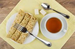 Te, pannkakor med välfyllt, socker, tesked och gaffel på servett Fotografering för Bildbyråer