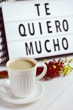 Te quiero mucho, I love you so much in spanish. Closeup of a white ceramic cup with coffee on a table, a bunch of flowers and a lightbox in the background with stock photography