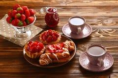 Te som dricker med tartlets och kakor med jordgubbar arkivbild
