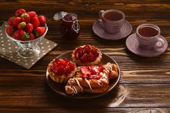 Te som dricker med tartlets och kakor med jordgubbar arkivfoton