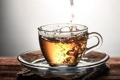 te som häller in i den glass genomskinliga koppen med bubblor på trätabellen Arkivfoton