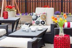 Te tjänade som på en utomhus- uteplats mellan blommor Arkivfoton