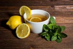Te - varm drink, citron, mintkaramell, säckväv, trä Arkivbild