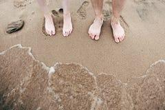 Te voet aan het zandige strand at high tide Stock Foto