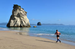 Te Whanganui-A-Hei (Cathedral Cove) Marine Reserve. WHITIANGA, NZL - Jan 20 2015: Man runs on the beach of Cathedral Cove.The area is very popular with tourists Stock Image