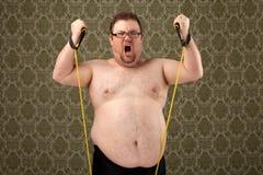 Te zwaar wit mannetje die met banden uitwerken Stock Foto's