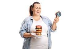 Te zware die vrouw met een stapel van donuts op witte achtergrond wordt geïsoleerd stock foto