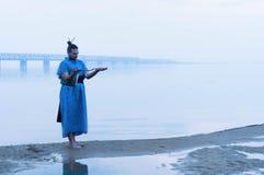 Te zware gebaarde mens in blauwe kimono die zich op rivierbank bevindt in mist die houten stok bekijkt royalty-vrije stock afbeeldingen
