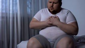 Te zware mens die aan borstpijn lijden, hoge bloeddruk, cholesterolniveau stock fotografie