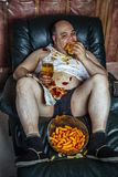Te zware mens die en op TV eten letten stock afbeeldingen