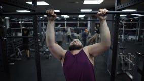 Te zware mens die op sportbar, zwakke lichaamsspieren, gymnastiek opleiding proberen uit te trekken stock footage
