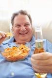 Te zware Mens die thuis Chips And Drinking Beer eten stock foto's