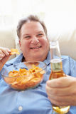 Te zware Mens die thuis Chips And Drinking Beer eten stock afbeelding