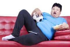 Te zware mens het letten op voetbalwedstrijd 1 Stock Fotografie