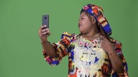 Te zware mooie Afrikaanse vrouw die traditionele kleding dragen tegen groene achtergrond