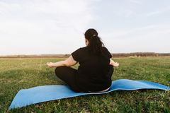 Te zware vrouw die bij yogamat in openlucht mediteren royalty-vrije stock fotografie