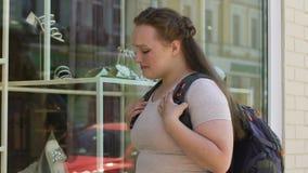 Te zware vrouw die droevig dure schoenen in het venster van de luxewinkel, droom bekijken stock footage