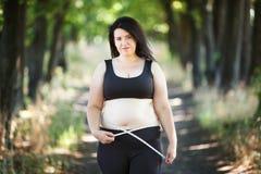 Te zware vrouw die haar buik met het meten van band meten, croppe Stock Foto