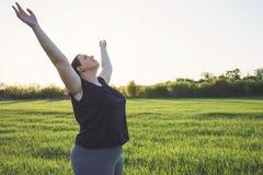 Te zware vrouw het praktizeren yoga op weide stock fotografie