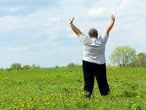 Te zware vrouw met handen omhoog op weide Stock Foto's