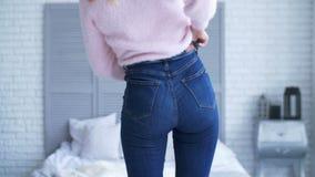 Te zware vrouwenmontage in strakke jeans in slaapkamer stock video