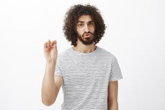 Te zwijgen gelieve Het portret van gehinderd en boos van knap mannelijk model met krullende haar en baard, het tonen houdt stil stock afbeelding