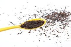 Tea. Black tea is broken up around the spoon Royalty Free Stock Images