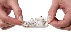 Tea. A woman holding a miniature coffee/tea set royalty free stock images
