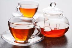 Tea. In transparent cup and pot Stock Photos