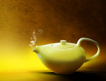Tea. A steaming yellow ceramic tea pot on a yellow and gold textured background Royalty Free Stock Image