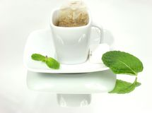Tea. Pure white tea cup with mint leaves on mirror background Stock Photography
