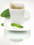 Tea. Pure white tea cup with mint leaves on mirror background Stock Image