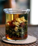 Tea. A glass containing blooming tea with green tea, jasmine and red lily Royalty Free Stock Photos