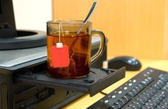 Tea. The cup of tea stands on the disk drive of a computer Stock Images