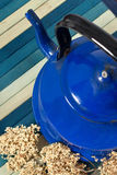 Tea. Blue old kettle for tea on blue background Royalty Free Stock Photos
